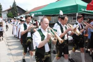 Mit bayrischer Blasmusik begleitet zieht der Trachtenverein durch Purfing